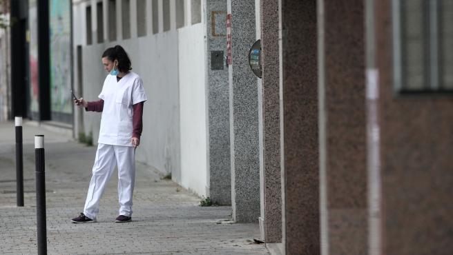 Una sanitaria con mascarilla consulta su móvil en la puerta del garaje del Hotel City House Florida Norte