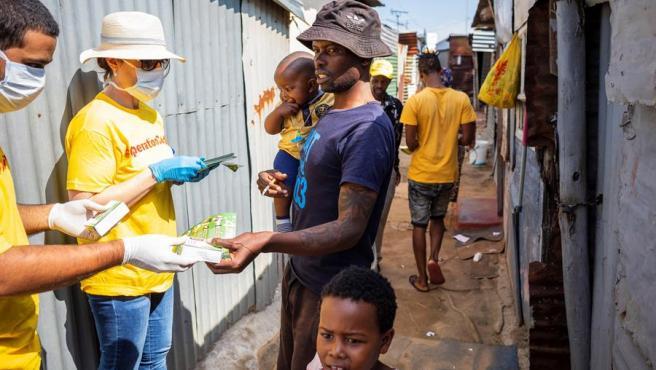 Un voluntario de una campaña contra el coronavirus reparte jabón en una barriada de Johanesburgo.