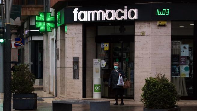 Una farmacia y una persona con mascarilla.