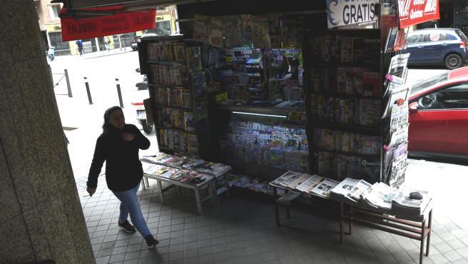 Una mujer pasa al lado en un quiosco abierto en el sexto día de confinamiento por coronavirus. Imagen de recurso de venta de prensa.