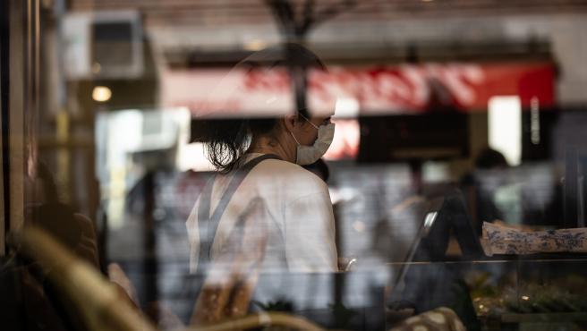 Una trabajadora atiende con una mascarilla protectora durante el primer día laborable de la segunda semana desde que se decretó el estado de alarma en el país a consecuencia del coronavirus, en Barcelona/Catalunya (España) a 23 de marzo de 2020.
