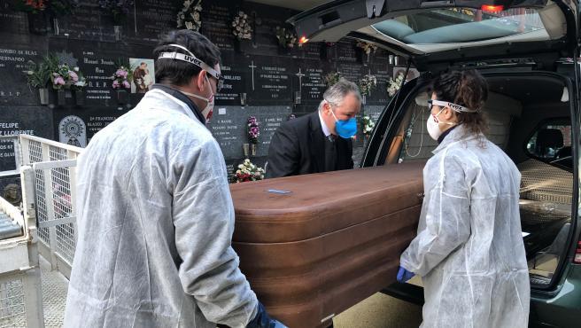 Maru Madurga, Oscar Herrero y un trabajador de una funeraria trasladan el ataúd con un fallecido por coronavirus para su entierro en un nicho