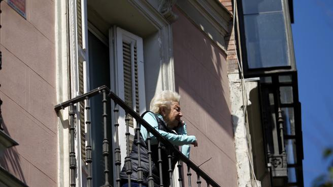 Una mujer observa el panorama desde su balcón para sobrellevar mejor el confinamiento por el coronavirus.