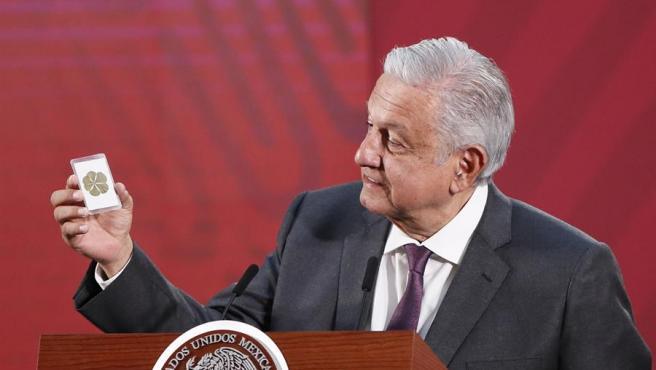 """El presidente de México, Andrés Manuel López Obrador, muestra una estampa con un trebol de seis hojas para representar el """"buen ánimo necesario"""" ante la crisis por el coronavirus, durante una rueda de prensa el 19 de marzo de 2020."""