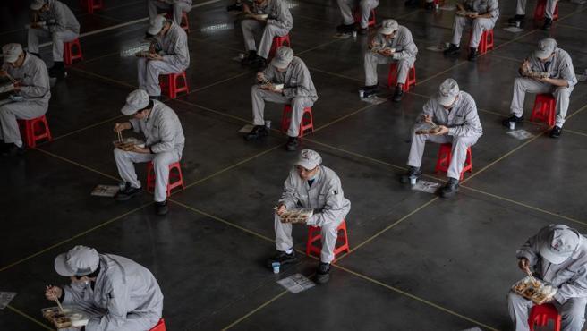 Trabajadores comen en asientos colocados para mantener la distancia recomendada para evitar contagios del coronavirus COVID-19, en la fábrica Dongfeng Honda en Wuhan, China.