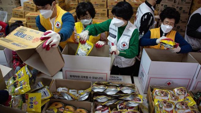 Miembros de la Cruz Roja de Corea del Sur preparan paquetes con alimentos y otros bienes de emergencia para vecindarios con necesidades debido a la crisis del coronavirus COVID-19.