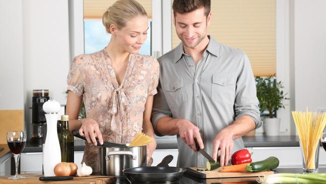 Dos personas preparando un plato en una cocina.