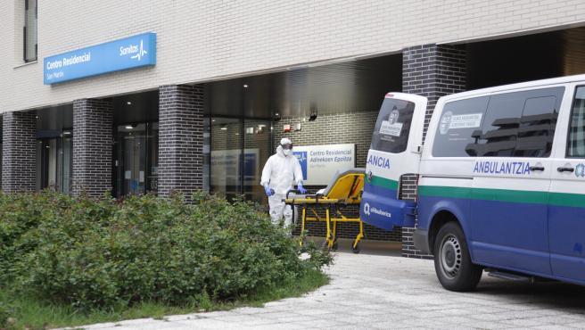 Un sanitario protegido con un traje, guantes y mascarilla, saca una camilla de una ambulancia en la entrada a la residencia donde han fallecido 8 personas por coronavirus.
