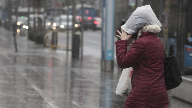 Una mujer se refugia de la lluvia con una bolsa de plástico, en Madrid (España), a 5 de marzo de 2020.