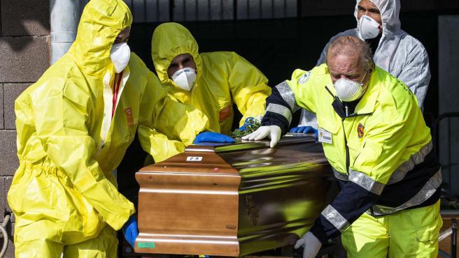 Los carabinieri y miembros del Ejército y Protección Civil cargan los ataúdes de fallecidos a causa del coronavirus.