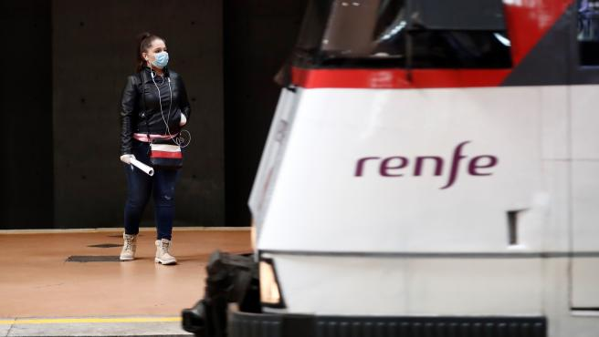 Una mujer con mascarilla espera la llegada de su tren.