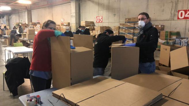 Diversas personas empaquetando el material para repartirlo.