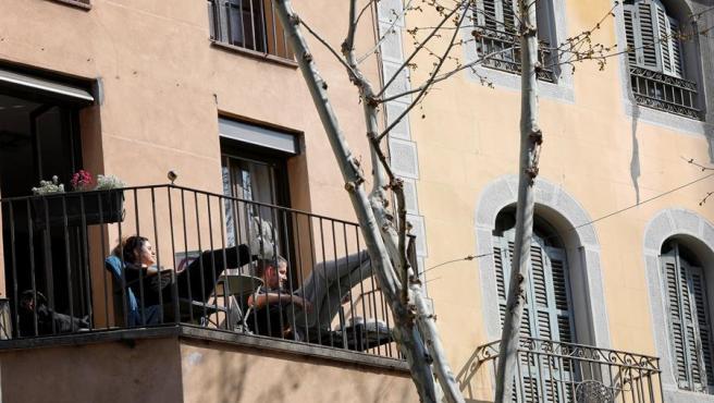 Una pareja toma el sol desde su balcón durante el cofinamiento por el coronavirus.