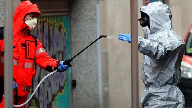 Un bombero de Barcelona desinfecta a un compañero tras salir de una residencia desinfectada.