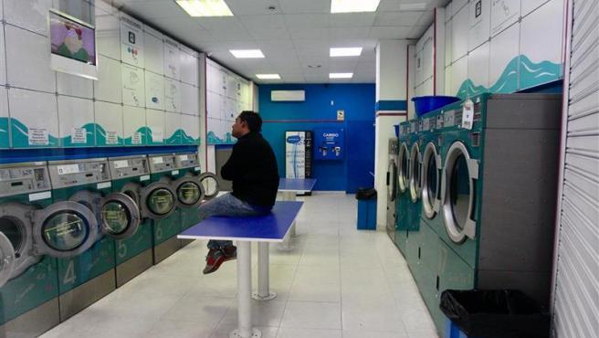 Un hombre observa la televisión en una lavandería de Madrid, uno de los pocos negocios fuera de los esenciales que permanecen abiertos.