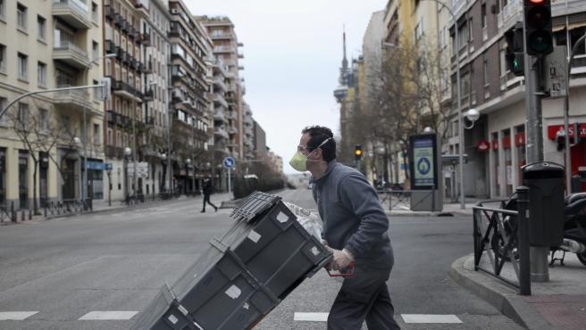 Un repartidor de supermercado traslada las cajas de un pedido, por una calle vacía en el centro de Madrid.