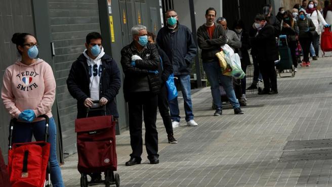 Varios clientes guardan cola para entrar en un supermercado de la Gran Via de Barcelona.