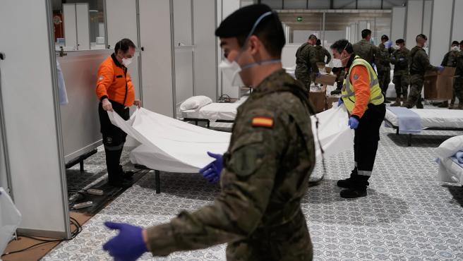 Militares y miembros de Protección Civil terminan de montar varias camas en el pabellón 7 de Ifema, uno de los tres que componen el hospital de campaña.