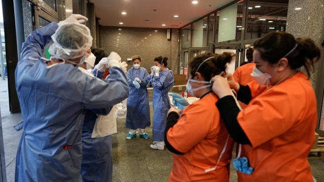 Sanitarios y trabajadores del hospital de campaña de Ifema se colocan las mascarillas antes de empezar a atender pacientes con coronavirus.