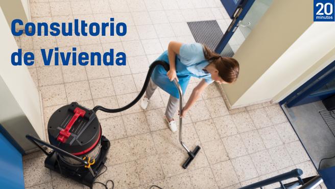 Una mujer limpia el rellano de un edificio