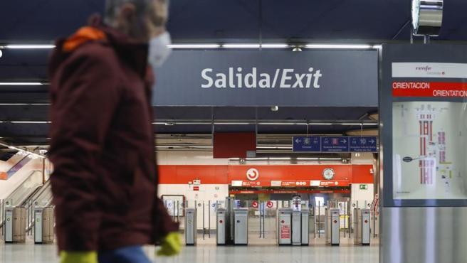 Un usuario de Cercanías Renfe protegido con guantes y mascarilla, en el intercambiador de Nuevos Ministerios, en Madrid, al inicio de la segunda semana de confinamiento por el coronavirus COVID-19.