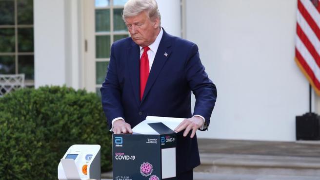 El presidente de EE UU, Donald Trump, abre una caja con material para realizar test del coronavirus COVID-19, durante una rueda de prensa en la Casa Blanca.