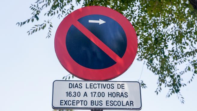 Señal de prohibido aparcar a la derecha (restricción de horas) excepto bus escolar.