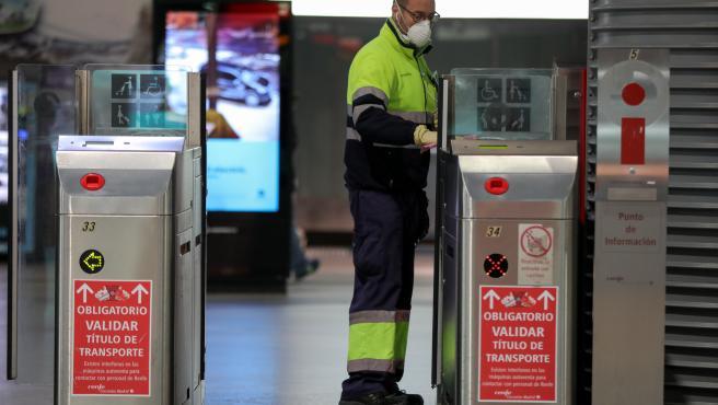 Un operario de limpieza desinfecta los torniquetes de la estación de cercanías Madrid Puerta de Atocha
