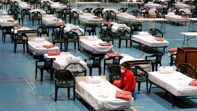 Miembros de la Cruz Roja instalan material en el pabellon de Les Comas de Igualada (Barcelona), reconvertido en un hospital de campaña para pacientes de coronavirus.