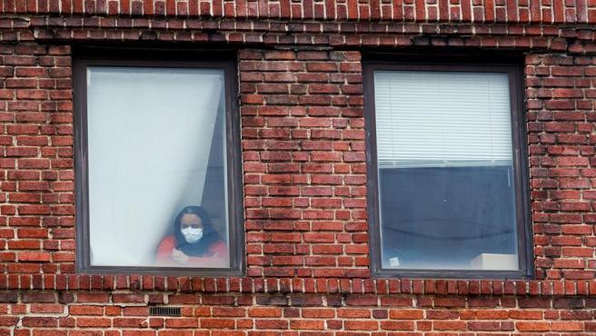Una empleada de un hospital en Brooklyn (Nueva York) observa el traslado de un fallecido por coronavirus a una morgue temporal, ante la falta de espacio en el centro sanitario.