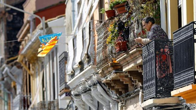 Una mujer se asoma a su balcón en Valencia.