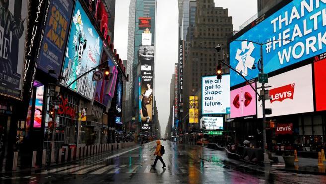 Un hombre camina por la plaza de Times Square, en Nueva York, totalmente vacía por las medidas adoptadas contra el coronavirus.