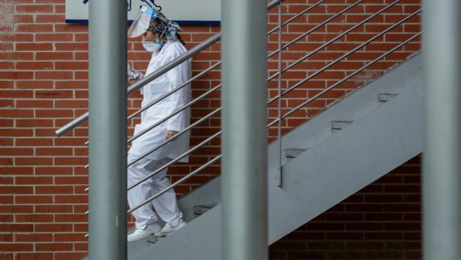 Una sanitaria protegida con mascarilla y pantalla protectora baja por unas escaleras del Hospital temporal de la Comunidad de Madrid habilitado en Ifema para pacientes con coronavirus.