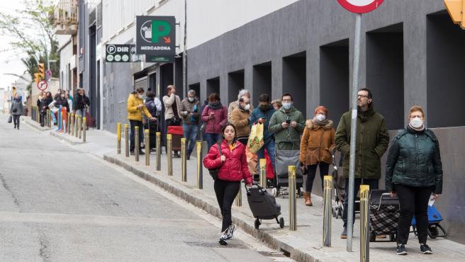 Varias personas esperan para entrar en un supermercado de Barcelona.