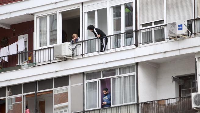 Varias personas en sus balcones a las 20 horas durante el confinamiento por el coronavirus en Madrid.