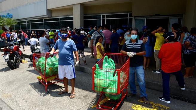 Cientos de personas se abastecen en un supermercado de Guayaquil (Ecuador), ante un posible toque de queda por la expansión del coronavirus en la ciudad.