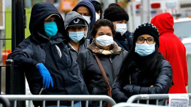Personas con mascarillas por el coronavirus hacen cola frente a un hospital en Queens, Nueva York.
