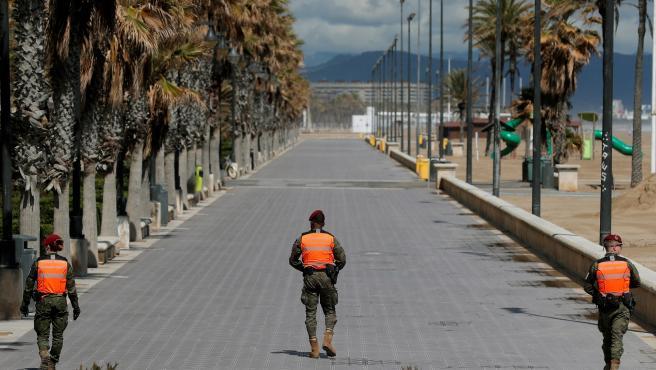 Tres policías militares patrullan por el paseo de la Malvarrosa en Valencia.