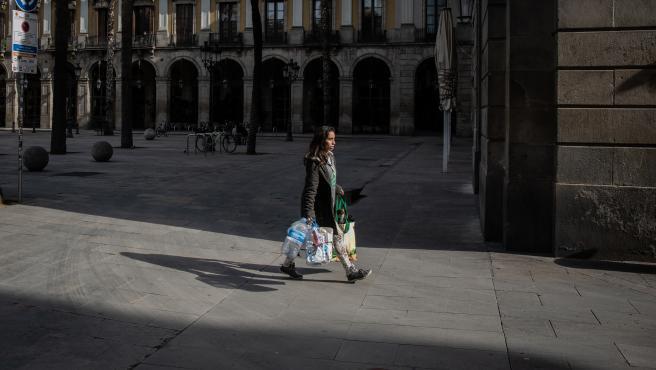 Una mujer anda con varias bolsas después de haber hecho la compra, durante el tercer día laborable del estado de alarma por coronavirus, en Barcelona/Catalunya (España) a 18 de marzo de 2020.