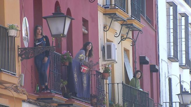 Vecinos de la trianera calle de Pureza (Sevilla) rezan el Ángelus a las puertas de la Semana Santa