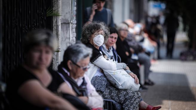Varias ancianas hacen cola a las puertas de un banco en Argentina.