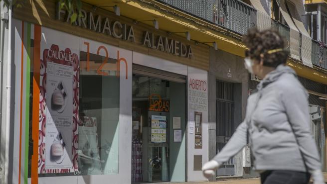 Una mujer con mascarilla frente a una farmacia.