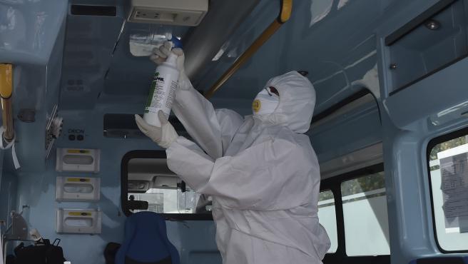Un trabajador desinfectado una ambulancia en Italia.