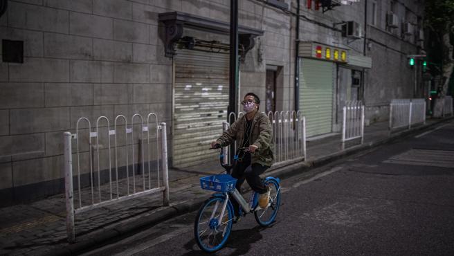 Un hombre chino pasea en bicicleta.