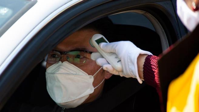 Un trabajador sanitario toma la temperatura a un conductor para detectar posibles síntomas de COVID-19, en Seúl, Corea del Sur.