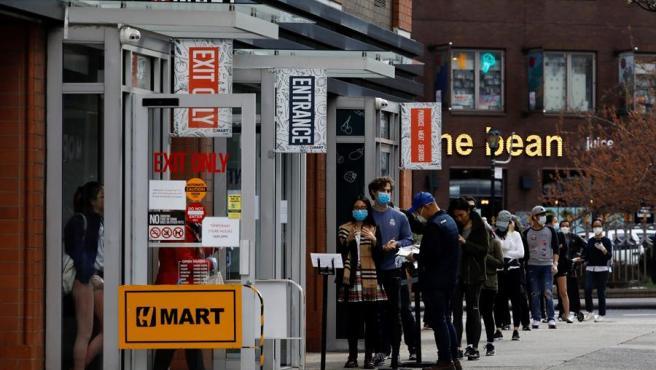 Varias personas con mascarillas por el coronavirus COVID-19 hacen cola frente a una tienda de comestibles en Nueva York, EE UU.