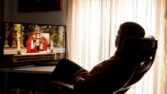 Una mujer sigue una misa televisada, durante el Domingo de Ramos, en su domicilio en Sevilla.