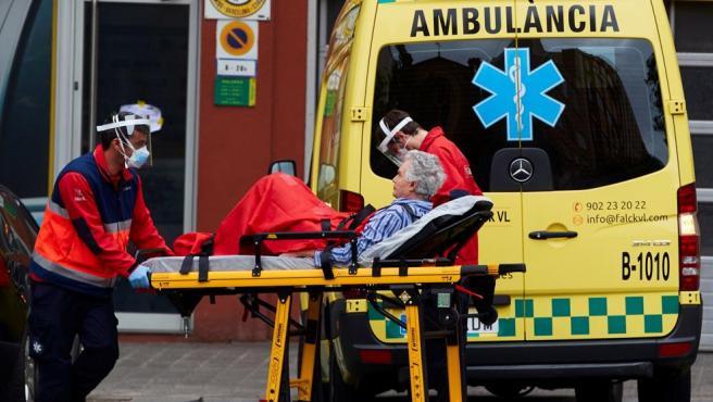 Operarios de una ambulancia transportan a un enfermo desde su domicilio en el centro de Barcelona