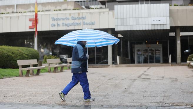 Un hombre con paraguas pasa frente a una oficina de la Tesorería General de la Seguridad Social