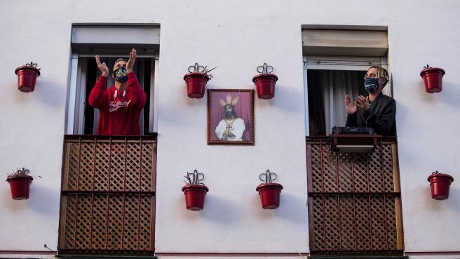 Vecinos del barrio de la Trinidad, junto a la casa de la Hermandad del 'Cautivo' de Málaga, aplauden este Lunes Santo.